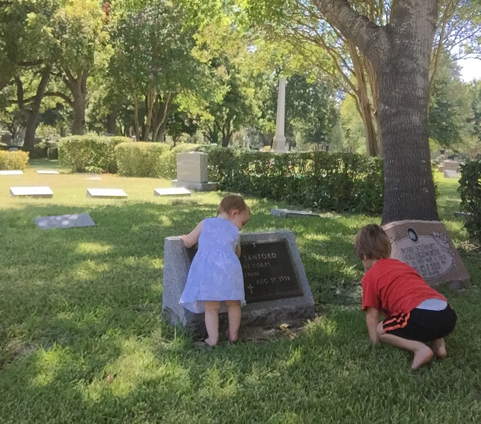 A toddler girl and small boy standing at a marine's grave